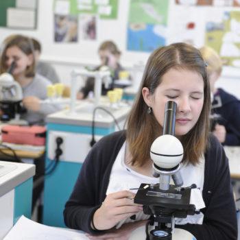 Jugend forscht: Mädchen schaut durch ein Mikroskop