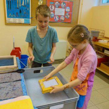 Zwei Kinder legen etwas in eine Kiste